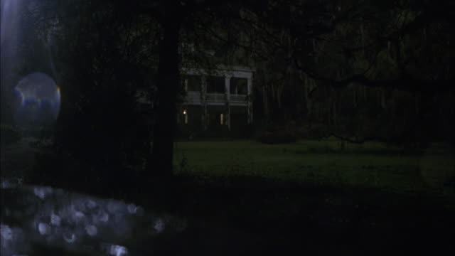 TRACKING SHOT, DRIVING POV 3/4 RIGHT FORWARD, CAR WINDOW WITH RAIN DROPS, CAR ARRIVING AS CLASSIC GREEK REVIVAL STYLE PLANTATION HOUSE OR MANSION, KNOTTY TREE BRANCHES.