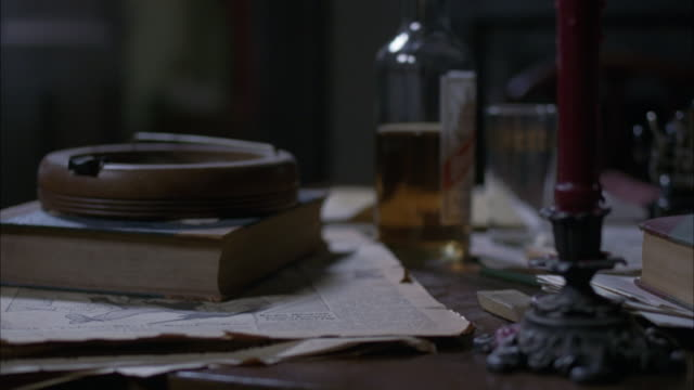 MEDIUM ANGLE OF HOME INTERIOR,  TABLE WITH ASHTRAY, BOOK, LIFE MAGAZINE, CANDLESTICK, BOTTLE OF LIQUOR.