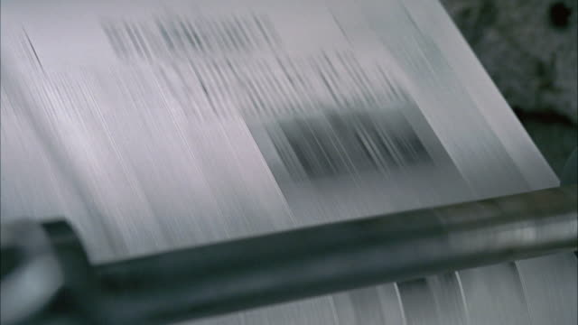 close angle of newspaper printing press seen printing dozens of copies of a newssheet. pulls back to medium mid-clip. - pressa da stampa video stock e b–roll