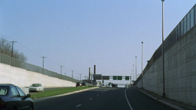 HAND HELD DRIVING POV OF AN INDUSTRIAL AREA.  A LONG ROAD GOES OVER A BRIDGE OR OVERPASS.