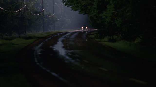 wide angle of vintage cars driving on rural area two lane road. headlights shine. near collision as one car passes second car. - headlight stock videos & royalty-free footage