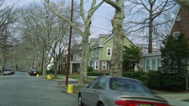 HAND HELD DRIVING POV THROUGH A MIDDLE CLASS NEIGHBORHOOD.  A RESIDENTIAL AREA LINED WITH TWO STORY HOUSES.