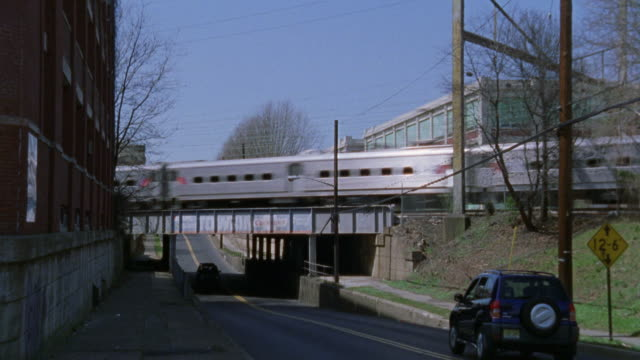 zoom in on a new jersey transit train driving over a bridge. railroads. - anno 2002 video stock e b–roll