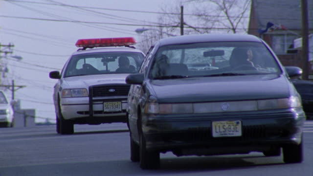 pull back as a police car follows another car about to get pulled over. - police car stock videos and b-roll footage