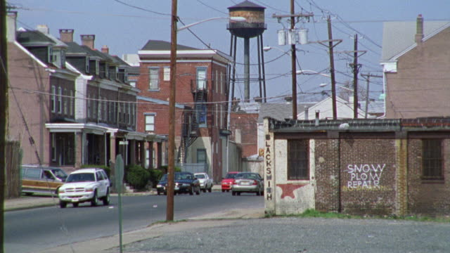 vidéos et rushes de wide angle of a road filled with cars in a lower class mixed residential area and industrial area.  houses, brick buildings, a water tower, and electrical wires everywhere. - new jersey