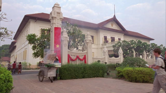 wide angle of two story government building with red flag with yellow star, communist vietnamese flag, hanging from ornate fence. - communist flag stock videos & royalty-free footage