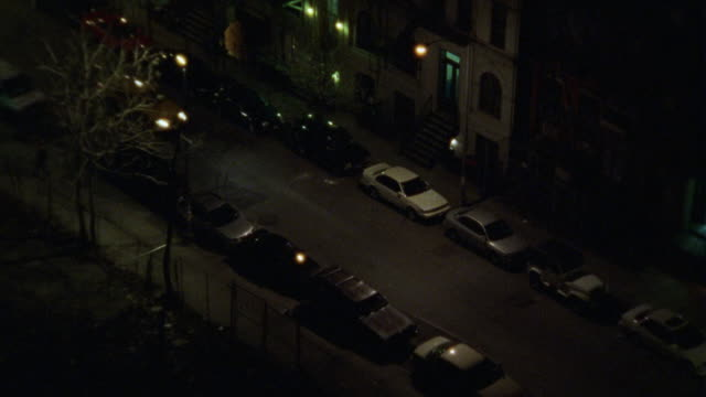 high angle down of a residential area. could be the village or the upper east side. a taxi drives through the upper class apartment buildings. - anno 2002 video stock e b–roll