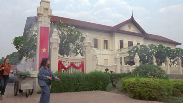 wide angle of two story government building with red flag with yellow star, communist vietnamese flag, hanging from ornate fence. - zweistöckiges bauwerk stock-videos und b-roll-filmmaterial