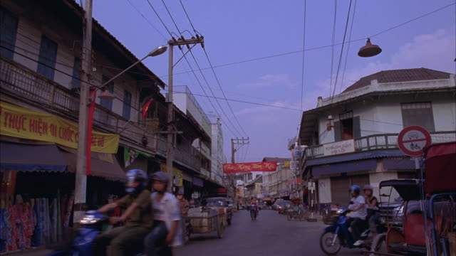 wide angle moving pov straight forward of intersection, vietnamese street with traffic, cars and couples on scooters, multi-story buildings with red and yellow banners strung across street. - chiang mai city stock videos and b-roll footage