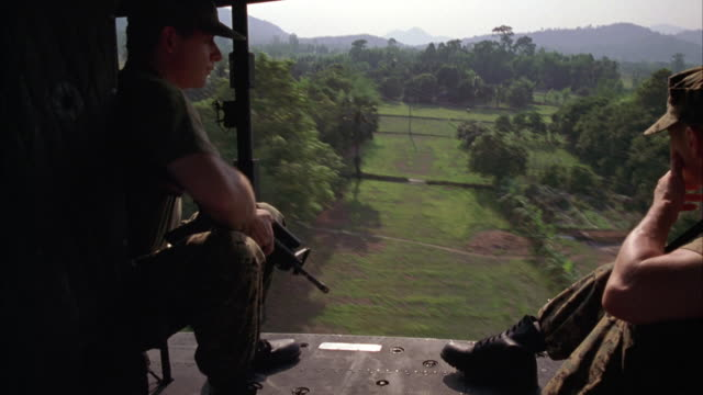 medium angle of military helicopter interior, as seen while chopper is in flight. army soldiers crouched with rifles. farmland or jungle landscape seen outside. - military helicopter stock videos and b-roll footage