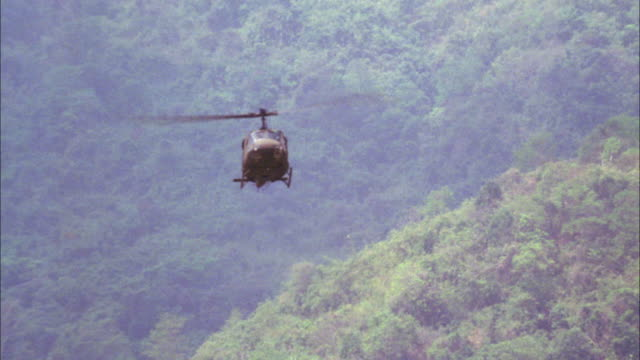 wide angle of military helicopter or army chopper flying over forest or jungle landscape. - military helicopter stock videos & royalty-free footage