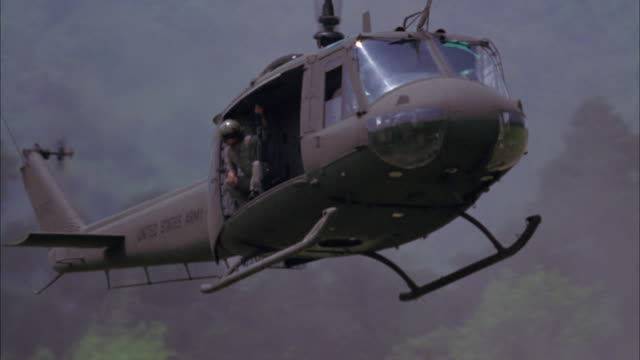 WIDE ANGLE OF MILITARY HELICOPTER FLYING OVER FOREST OR JUNGLE LANDSCAPE, LANDING. ARMY SOLDIER SEEN.