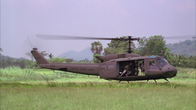wide angle of military helicopter flying over forest or jungle landscape, landing. army soldier seen. - military helicopter stock videos & royalty-free footage
