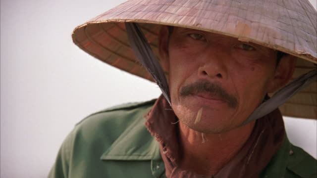 close angle of chinese man wearing grass or bamboo sun hat. - sonnenhut stock-videos und b-roll-filmmaterial