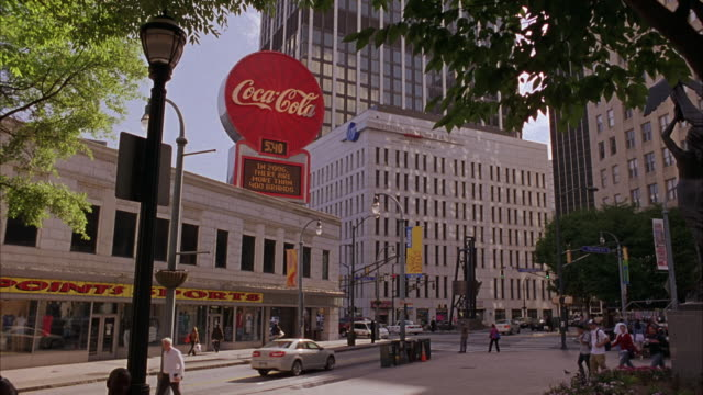 HAND HELD OF DOWNTOWN ATLANTA STREET CORNER, PEOPLE WALKING, LARGE COCA COLA BILLBOARDS, SPORTING GOODS STORE, CARS, SKYSCRAPERS. MULTISTORY BUILDINGS.