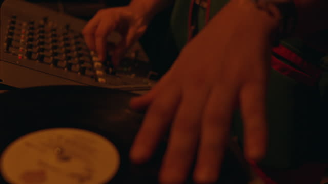 CLOSE ANGLE OF RECORD PLAYER, DISC JOCKEY'S HAND SCRATCHING RECORDS, CONTROL PANELS.  MUSIC.