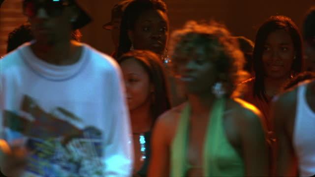 HAND HELD OF YOUNG WOMEN, MEN DANCING IN BAR, DANCE CLUB, TAVERN OR NIGHTCLUB. MUSIC. LIGHTS OVERHEAD.