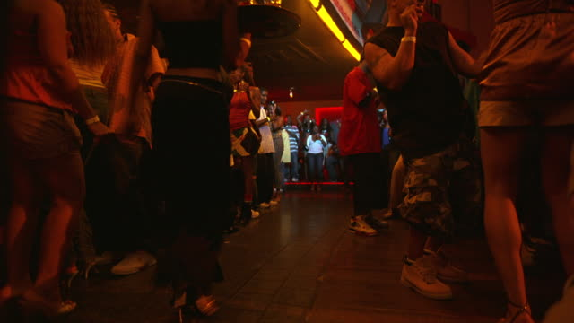 WIDE ANGLE OF YOUNG WOMEN, MEN DANCING IN BAR, DANCE CLUB, TAVERN OR NIGHTCLUB.  MUSIC. WAITRESS.