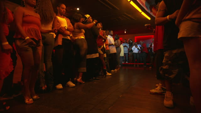 WIDE ANGLE OF YOUNG WOMEN, MEN DANCING IN BAR, DANCE CLUB, TAVERN OR NIGHTCLUB.  MUSIC.