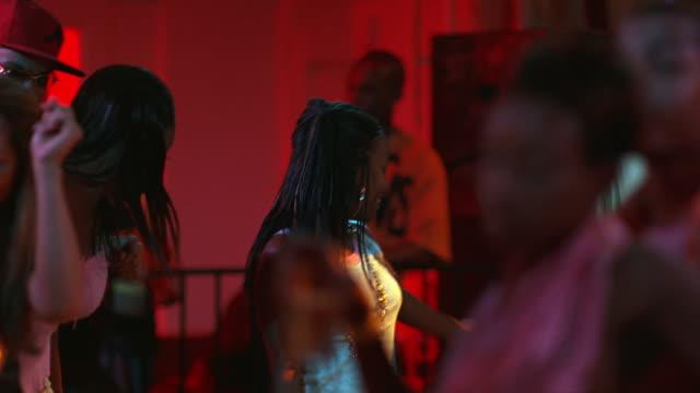 HAND HELD OF YOUNG WOMEN, MEN DANCING IN BAR, DANCE CLUB, TAVERN OR NIGHTCLUB.  MUSIC.