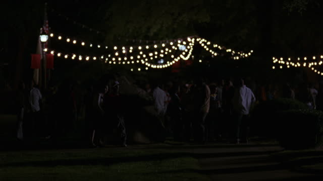 medium angle of group of young men and women, college students gathered on lawn outside dorm, sorority or fraternity on college campus. - keg stock videos and b-roll footage