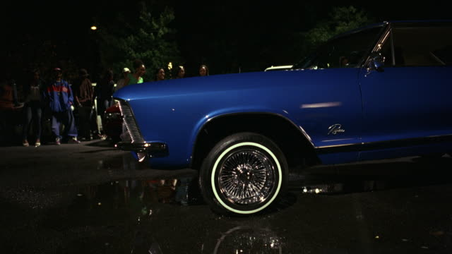 MEDIUM ANGLE OF BLUE CLASSIC CAR IN PRISTINE CONDITION BOUNCING WITH HYDRAULICS IN A PARKING LOT. WATER PUDDLES ON CONCRETE.
