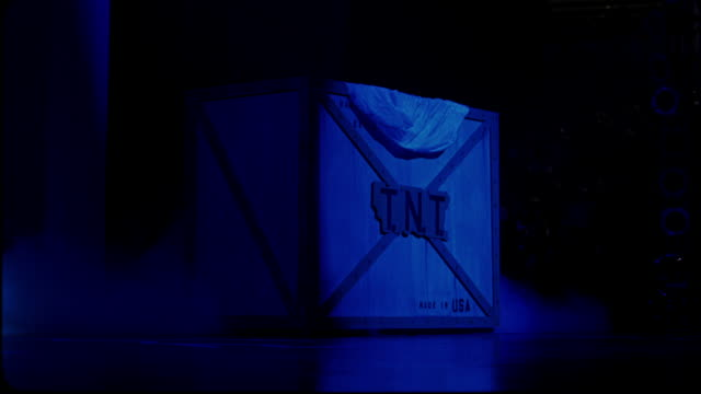 """vídeos y material grabado en eventos de stock de close angle of a large wooden box with metal framing on a stage in an arena, stadium, or auditorium. box reads """"t.n.t."""" and """"made in usa."""" box bathed in blue light. - anfiteatro"""