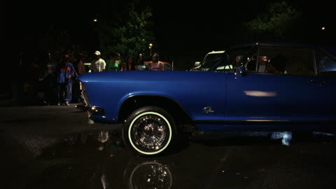 medium angle of blue classic car in pristine condition bouncing with hydraulics in a parking lot. water puddles on concrete. - bouncing stock videos & royalty-free footage