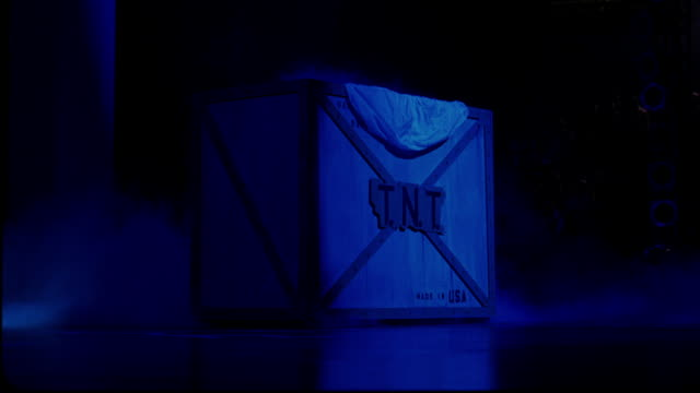 "close angle of a large wooden box with metal framing on a stage in an arena, stadium, or auditorium. box reads ""t.n.t."" and ""made in usa."" box bathed in blue light. - made in usa点の映像素材/bロール"