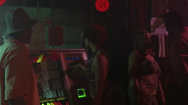 medium angle of dark bar, young woman using jukebox, men women hanging out. taverns. pool halls. - jukebox stock videos & royalty-free footage