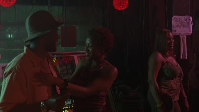 medium angle of dark bar, young woman using jukebox, men women hanging out, dancing. taverns. pool halls. - jukebox stock videos & royalty-free footage