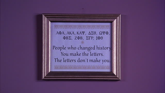 MEDIUM ANGLE OF INSPIRATIONAL PLAQUE WITH GREEK LETTERS, FRATERNITY QUOTE. PAN BACK AND FORTH TO MARTIN LUTHER KING JR PHOTOGRAPH.