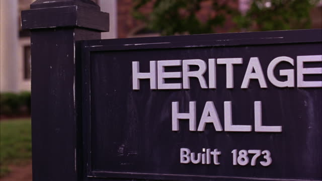 "medium angle of sign for ""heritage hall."" college campuses, universities, classroom buildings. brick building with white columns in background. - georgia stati uniti meridionali video stock e b–roll"