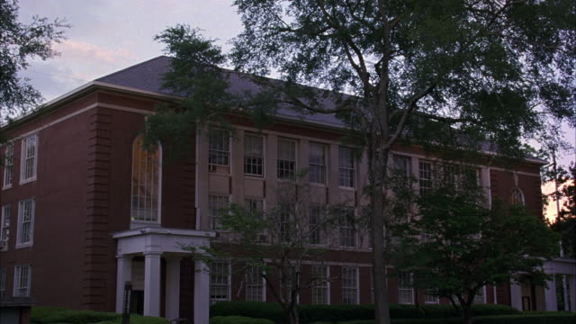 MEDIUM ANGLE OF THREE STORY BRICK BUILDING WITH WHITE COLUMNS AND TREES. COLLEGE CAMPUSES, UNIVERSITIES, CLASSROOM BUILDINGS.