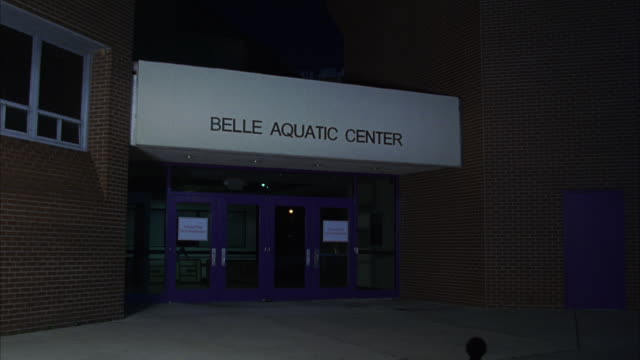 WIDE ANGLE OF BRICK BUILDING WITH SIGN 'BELLE AQUATIC CENTER.' COULD BE COLLEGE SPORTS CENTER, YMCA TYPE OF BUILDING WITH INDOOR POOL WHERE SWIM TEAM WOULD MEET. SERIES.
