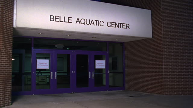 WIDE ANGLE OF BRICK BUILDING WITH SIGN 'BELLE AQUATIC CENTER.' COULD BE COLLEGE SPORTS CENTER, YMCA TYPE OF BUILDING WITH INDOOR POOL WHERE SWIM TEAM WOULD MEET.