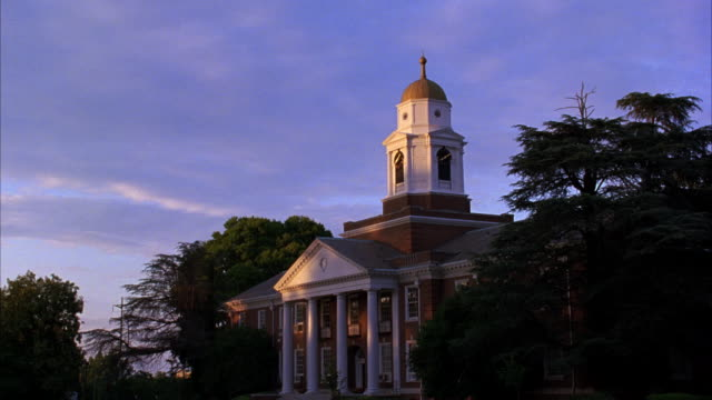 WIDE ANGLE OF MULTI-STORY BRICK BUILDING WITH COLUMNS, WHITE CLOCK TOWER. THIS STATELY BUILDING COULD BE COLLEGE CAMPUSES, UNIVERSITIES, GOVERNMENT BUILDING, OR PERHAPS A CITY HALL.