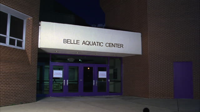 PAN DOWN OF BRICK BUILDING WITH SIGN 'BELLE AQUATIC CENTER.' COULD BE COLLEGE SPORTS CENTER, YMCA TYPE OF BUILDING WITH INDOOR POOL WHERE SWIM TEAM WOULD MEET. SERIES.