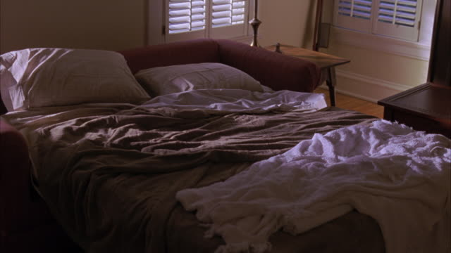 vidéos et rushes de medium angle of messy bed or sofa bed, shutter style window blinds. small bedroom. - messy bedroom