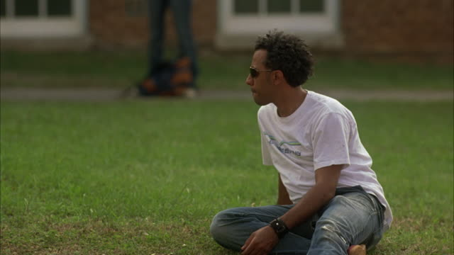 MEDIUM ANGLE OF YOUNG MAN SITTING ON GRASS LAWN OF CAMPUS OF COLLEGE OR HIGH SCHOOL. COULD BE STUDENT.