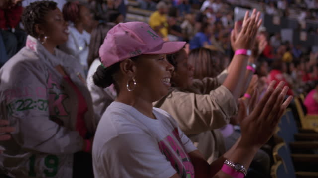 medium angle of women wearing pink tee shirts, hats, wrist bands sitting in bleachers cheering and clapping in sports arena or stadium. - cheering stock videos & royalty-free footage