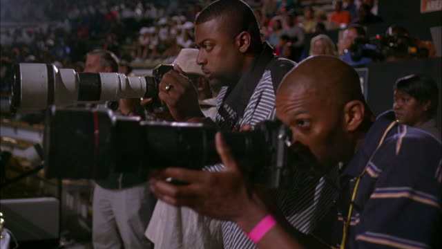 hand held of judges, press box, photographers in sports arena. men with laptops and phones, cameramen. spectators, crowds in bleachers in background. - fotograf stock-videos und b-roll-filmmaterial