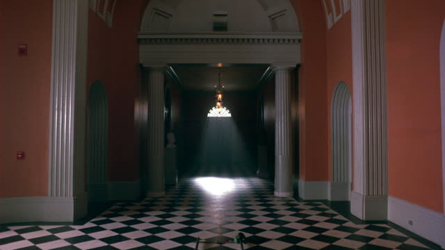 WIDE ANGLE OF HALLWAY IN UPPER CLASS HOME, MANSION, OR MUSEUM. FRONT DOOR SEEN AT END OF GRAND ENTRY WAY WITH COLUMNS, BLACK AND WHITE CHECKERED FLOOR AND PINK WALLS. STATELY BUILDING COULD ALSO BE PART OF COLLEGE.