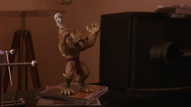 close angle of figurine of wolf man creature holding club. could be mascot. - figurine stock videos and b-roll footage