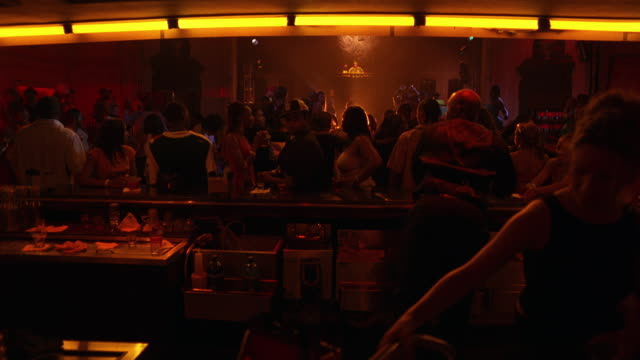wide angle, forward moving pov of crowded bar area in nightclub or discotheque. women and men dancing, drinking. trendy. - pub stock videos & royalty-free footage