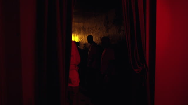 wide angle of hallway in crowded bar or nightclub.  women and men. hip cool trendy club. red curtains on walls. - 2006年点の映像素材/bロール