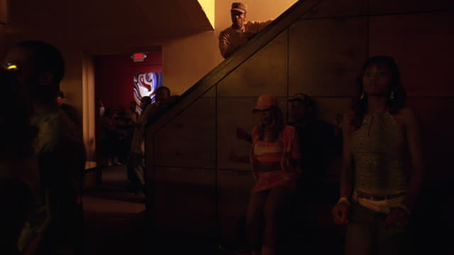 wide angle of staircase area in nightclub bar or tavern. women and men dancing, red lights. people watching dance floor. spotlights. - 2006年点の映像素材/bロール