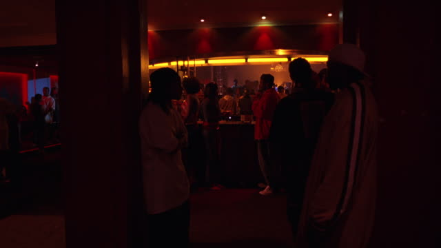 medium angle, forward moving pov of waitress walking through crowded bar area in nightclub, discotheque. women and men dancing, drinking.trendy. - 2006年点の映像素材/bロール