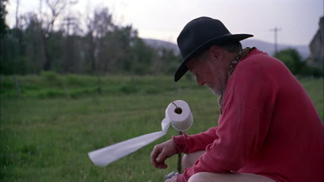 medium angle of man wearing brown felt western-style or cowboy hat and dirty red long-sleeve pullover shirt seated on outdoor toilet next to branch with roll of toilet paper blowing in wind or breeze. grass, trees and country road in bg. - sleeve stock videos and b-roll footage