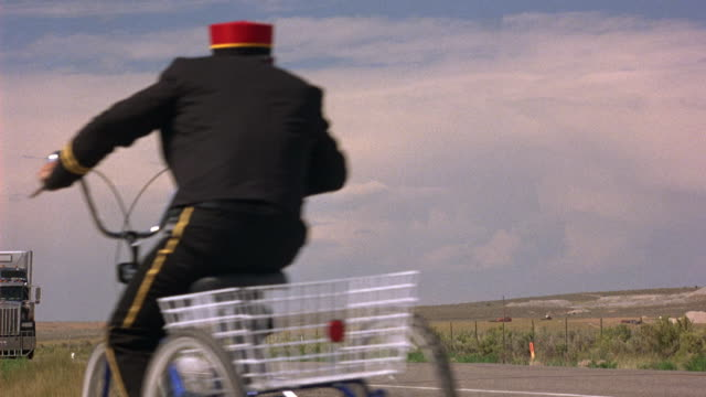 vídeos y material grabado en eventos de stock de wide angle of two lane road or highway through prairie landscape. hills and low clouds. cloudy sky. overcast. tall grass borders road. bellhop on bicycle with basket swerving at side of road as semi truck nears. - hospitalidad